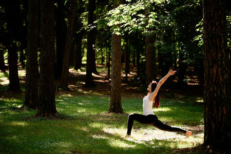 outdoor exercise: Young beautiful red-haired girl does yoga in Park on green background. Relaxation.
