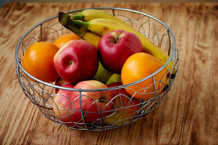 Metal fruit bowl on a wooden surface. Close. Bananas, oranges apples Stock Photo