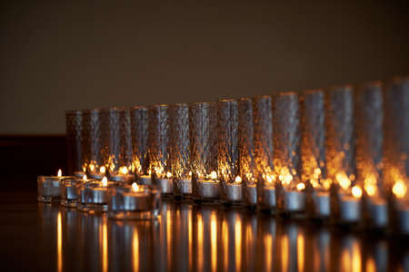 Many burning candles in transparent glasses, shiny floor, the reflection. Mood, relaxation, prayer and comfort