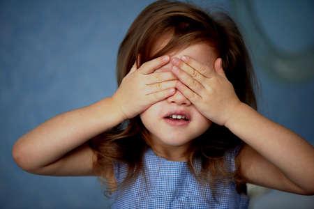 ない邪悪な女の子を参照してください。赤ちゃんが手で目をカバーします。