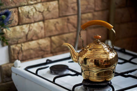 old gas stove: Copper kettle stands on an old vintage plate. Kitchen Stock Photo