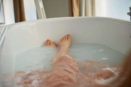Legs resting in the tub of a person. Cleopatra bath with milk. Beauty relaxation