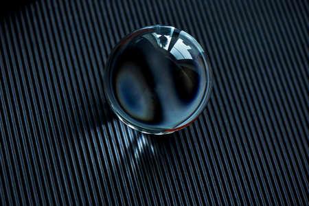 Globo de cristal o gota de agua sobre un papel corrugado de grafito oscuro. Limpia y brilla Foto de archivo