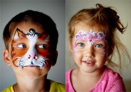 Garçon de 6 ans aux yeux bleus, maquillage d'un chat ou d'un tigre. Jolie fille excitante aux yeux bleus de 2 ans avec un maquillage Banque d'images - 77006477
