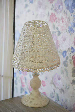 antique furniture: white openwork metal table lamp stands on a bedside table. Bright interior. Shabby chic