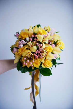 Fresh yellow bouquet of yellow roses and pink berries. Bright colors