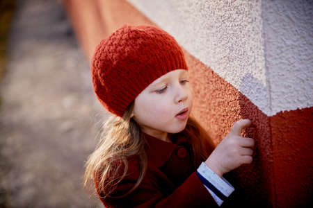 Baby 3 years with long hair. In a red beret and coat outside in the sun. Picking his . Childhood Stock Photo