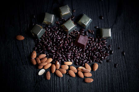 sunflower seeds: Candy in Golden foil, almonds and sunflower seeds in chocolate lying on a dark background. Studio