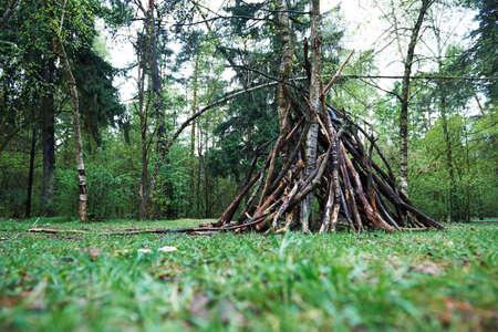 숲에 나뭇 가지의 오두막입니다. 자연, 생존, 삶의 법칙