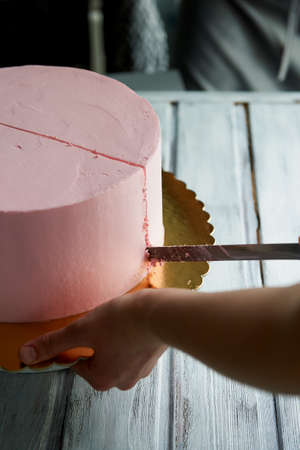 The pastry chef cut the cake with a long knife. Hands care. Cut a pink cake in a minimalist style without ornaments.