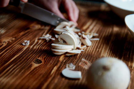 People cut mushrooms with a knife. The slices are adjacent. Wooden surface