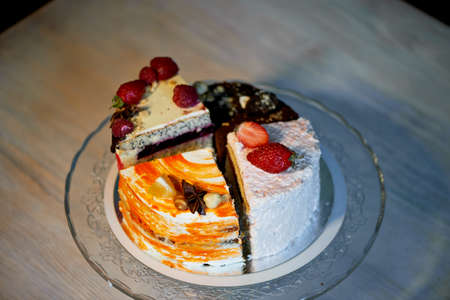 The different pieces of the cake smoothly rotate on the base.There is chocolate, carrot, yogurt and berries.
