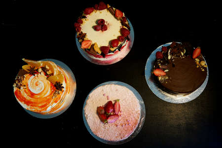 The different cakes smoothly rotate on the base. There is chocolate, carrot, yogurt and berries.