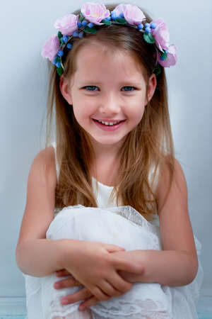pinched: Charming girl with long ash-blond hair , lively blue eyes and a pinched nose, the bezel is handmade . Smiling, holding your hands up.Smiling and looking at camera