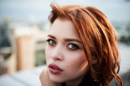 Beautiful red-haired girl with plump lips. Walking around the city. A natural beauty. Roof. Ginger Stock Photo