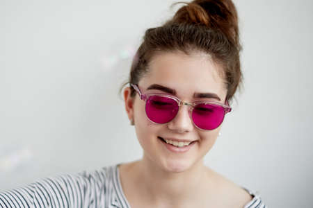 The girl smiles happily in the pink glasses. A naive view of the world in the transition to adulthood