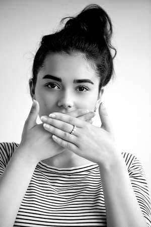 Emotions. Close-up facial portrait. Speak no evil. Girl on a light background closes his mouth