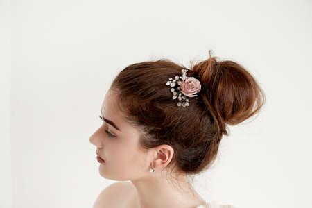 Portrait de belle fille aux cheveux noirs et une peau de porcelaine claire. Cheveux en chignon. Accessoire de cheveux à la main Banque d'images