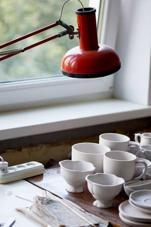 The workplace of ceramist. Baked dishes, ready for painting. A window table with a red lamp