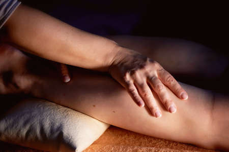 Sesame oil massage for calf muscle. Relaxation treatment for young female, close up. Sports massage - Leg massage - Physical therapist doing massage of calfs, applying strong finger pressure. Toned image, selective focus. Horizontal view of masseur massag