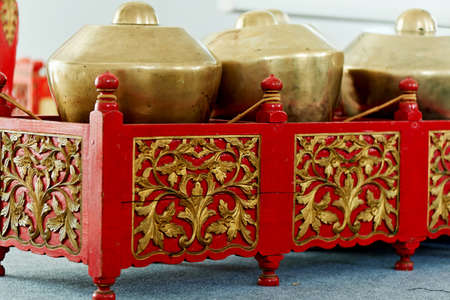 Indonesian traditional musical instruments. A metal drum. Red twisted stand
