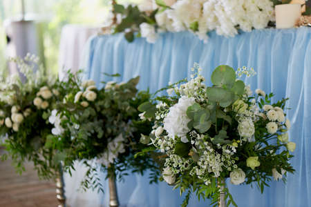 decorate: Stylish, fashionable wedding arch ceremony decorated with blue and white different flowers. Floral Design. Summer restaurant outdoors by preparation for wedding background on the river or sea.