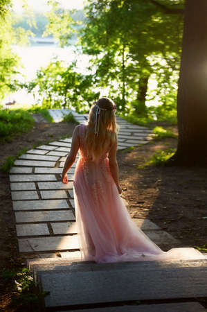 Silhouette swirling in the setting sun in the beautiful woods of the bride in the peach dress with lace. Blonde with a good figure.The feeling of happiness and serenity