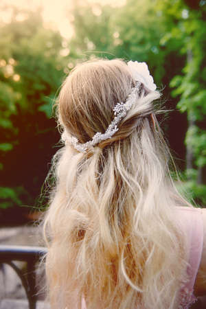 Portrait of a beautiful bride blond girl in pink lace dress ,hair decoration, handmade. Tenderness. Rear view, focus on the hair