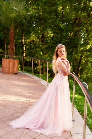 Portrait of a beautiful bride blond girl in pink lace dress ,hair decoration, handmade. Tenderness. Standing in the midst of a dark forest green in the rays of the setting sun. Shows a long dress with a train Stock Photo