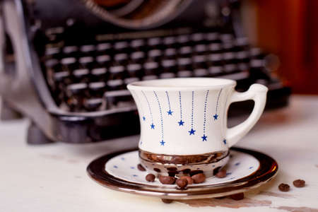 Old metal typewriter, covered in dust and rust. Cup of coffee on the table. The atmosphere of comfort and creativity. Retro