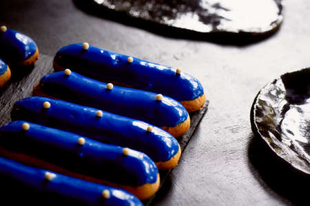 Blue eclairs with a mirrored glaze. A work of culinary art. Cakes Stock Photo