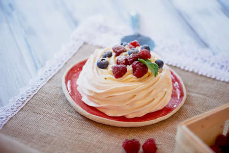 Dessert Anna Pavlova with raspberries and blueberries on white wooden surface