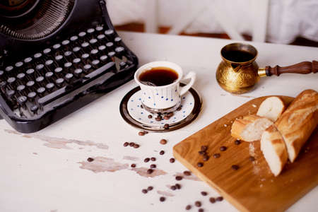 Workplace creative writing person. Typewriter, coffee baguette