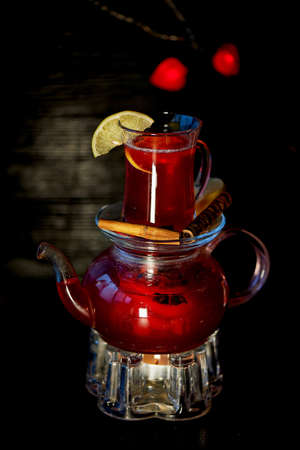 The atmosphere of new year atmosphere. Kettle on stand with warming candles. In a kettle of mulled wine or hibiscus tea with lemon. Cinnamon sticks and orange.