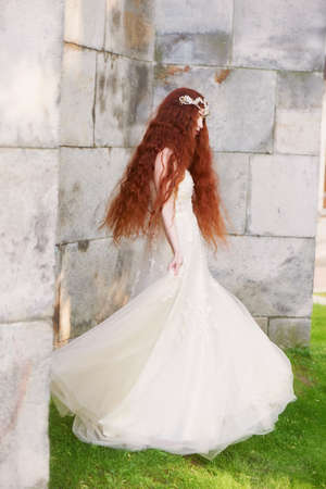 Beautiful red-haired girl with long curly hair in the bride, in a long lace dress. A natural beauty. Stok Fotoğraf