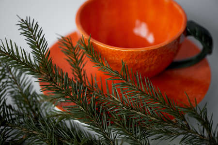 Juicy orange tea pair on the background of fir branches. A feeling of freshness and anticipation of the New year