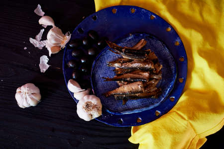 Yellow blue contrast gamma. Sprat on the blue plate on the yellow napkin. Framed with garlic and olives