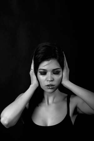 Young beautiful girl closes the ears. Hear no evil, black-white