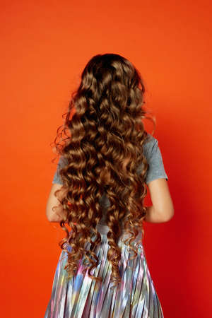 Girl on orange background in the Studio. Very long curly hair like in a fairy tale. Rapunzel 스톡 콘텐츠
