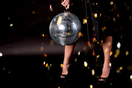 Feet in shoes, dark background. Disco ball. The atmosphere of celebration and dancing