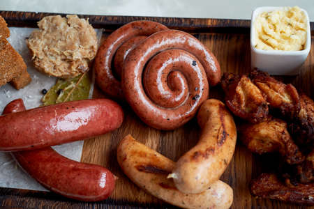Meat set for a large company on a wooden stand. Grilled sausages, sauerkraut, French fries and sauces