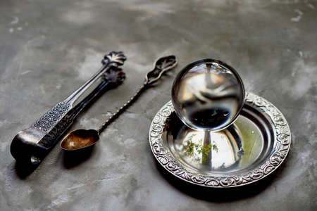 the glass ball lies on an old saucer. Old appliances. Grey concrete background Stock Photo
