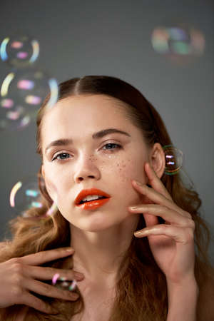Portrait of young beautiful girl in Studio, with professional makeup. Beauty shooting. The beauty of soap bubbles. The rainbow flares Stock Photo
