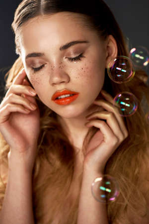Portrait of young beautiful girl in Studio, with professional makeup. Beauty shooting. The beauty of soap bubbles. The rainbow flares Banco de Imagens