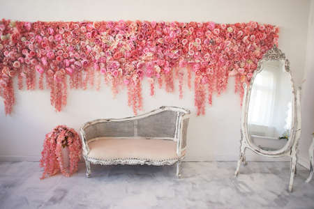 Old carved daybed with soft upholstery against a white wall decorated with pink flowers. Gorgeous garland. The interior decor is romantic, wedding photo zone. Imitation in the mirror. Full-length mirror Foto de archivo