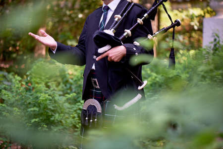A man with a bagpipe, a kilt in a cage with a green and red stripe. Culture Stock fotó