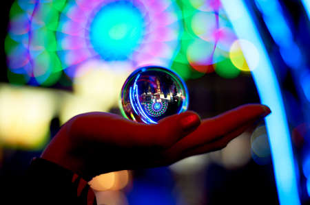 Ferris wheel through a glass ball on the palm of your hand. The atmosphere of celebration and rest. Evening adventure. Bright color. Hand silhouette