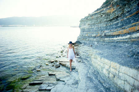A beautiful girl in a white tunic walks along the Bay of the sea, rocky shore. On her head a black wide-brimmed hat. Freedom and serenity