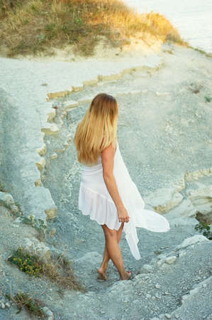 Girl goes on coastal desert path, with dried grass. Blonde in a white tunic. The theme of the desert and the sea