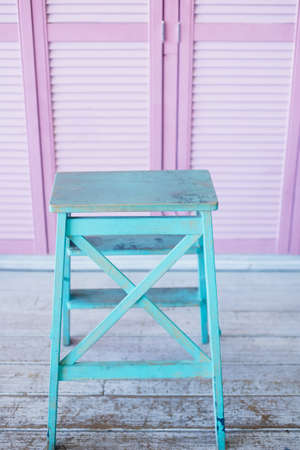 Turquoise stepladder on a pink background of doors blinds. Combination of color